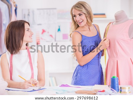 Brown hair and blond hair women looking to each other and smiling. - stock photo