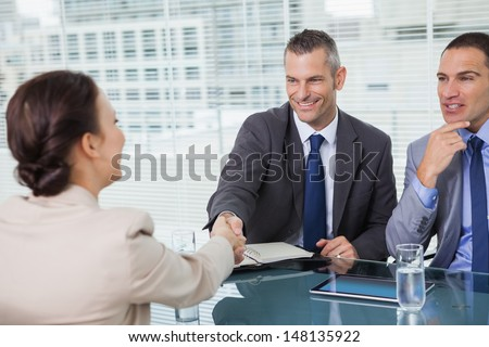 Brown haired woman shaking hands with her future employer in bright office - stock photo
