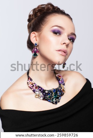 Brown-haired young woman in black dress and with bijouterie on gray background - stock photo