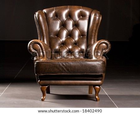 Brown leather armchair on a black background