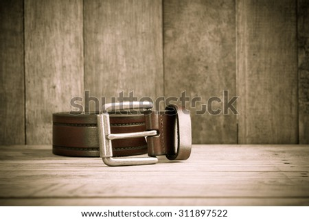 brown leather belt abandoned on wooden floor background ,Retro style - stock photo