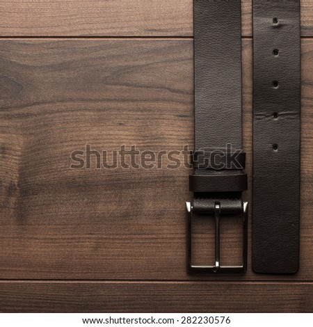 brown leather belt for men on wooden table - stock photo