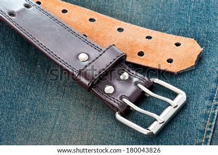 Brown leather belt of vintage blue jeans  - stock photo