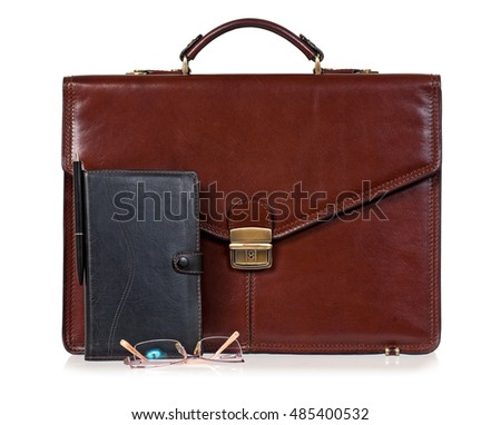 Brown leather briefcase with office accessories - notepad and eyeglasses, isolated on white background