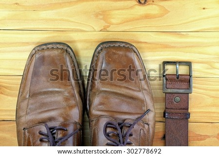 Brown leather men's shoes and belt on a wooden board. Men fashion. Men accessories.  - stock photo