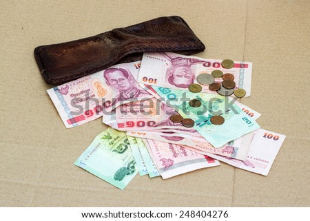 brown leather money wallet with full thai baht paper money and coin on cardboard