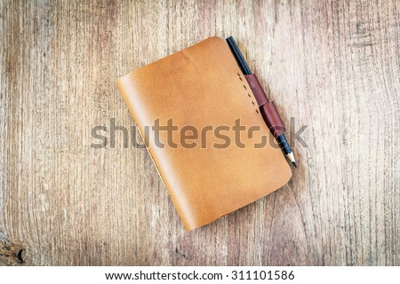 brown Leather notebooks on wooden background - stock photo
