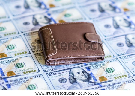 Brown leather wallet on stacks of the United States dollar  - stock photo