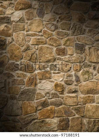 Brown masonry rock wall lit diagonally
