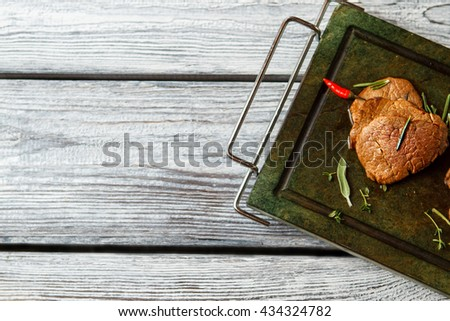 Brown meat and chili pepper. Meat on dark green tray. Spicy meal for a gourmet. Veal medallions with fresh herbs. - stock photo