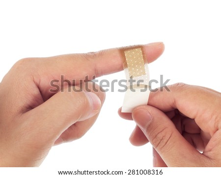 Brown medicine bandage on injured finger on white background.
