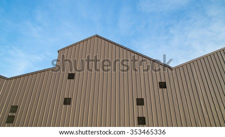 Brown metal sheet for industrial building and construction on blue sky background. - stock photo
