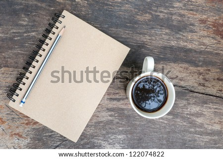 brown note book with coffee cup on grunge wood - stock photo