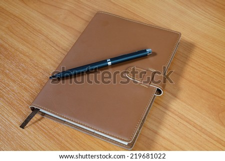 brown notebook and pen over wooden background - stock photo