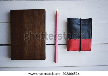 Brown Notebook  with pensil and porse on white wooden background. - stock photo