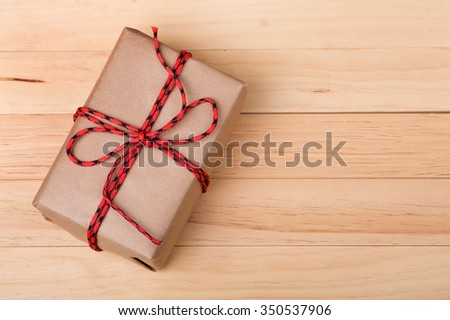 Brown package tied with red string on wood background