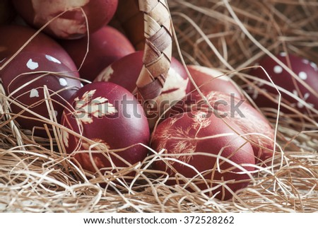 Brown painted Easter eggs with natural grass pattern spill out of a wicker basket on an old wooden background with straw, still life in rustic style, selective focus - stock photo