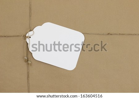Brown paper package with large blank tag - stock photo