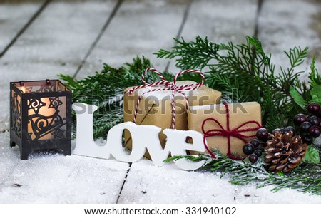 Brown paper packages tied up in string, Christmas tree garland, candle, Love and snow on antique rustic wooden background - stock photo