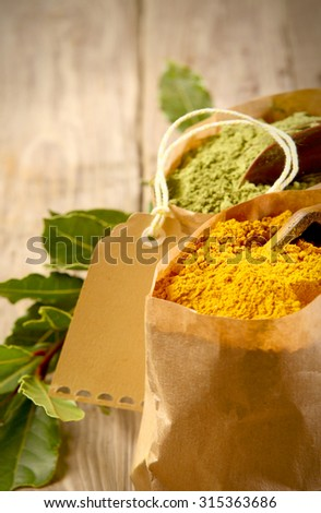 Brown paper packet of colorful dried turmeric powder, a pungent spice used in curry and Asian and Oriental cuisine, close up view with a blank tag behind over a rustic wood background - stock photo