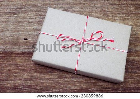 brown paper parcel tied with red and white string on wood table - stock photo