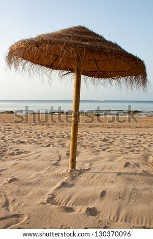 Brown Parasol at the beach made out of straw - stock photo