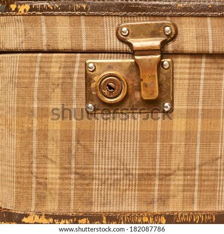Brown plaid cloth suitcase bag lock fragment - stock photo