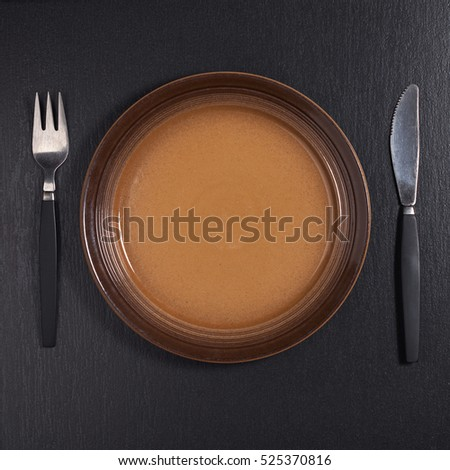 Brown plate with fork and knife on black stone table, top view
