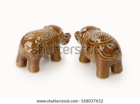 Brown porcelain elephants on white background - stock photo