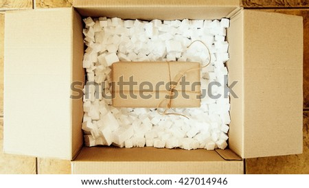 Brown present box in big shipping box. Opening a parcel contains a gift. Unpacking box with another box. Surprise. People, delivery, shipping service, opening cardboard box or parcel at home. - stock photo