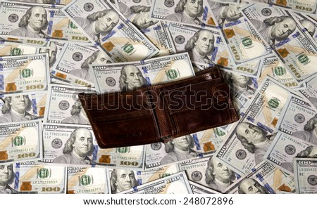 Brown purse (wallet) on american money backdrop / photography of the United States dollar (U.S. dollar, American dollar, US Dollar) - the official currency of the United States  - stock photo
