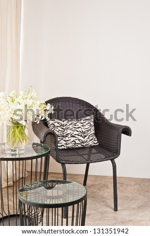 Brown rattan Chair in interior setting in front of a white wall - stock photo
