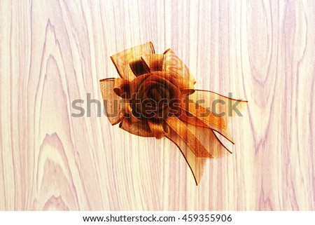 brown ribbon with artificial wooden background - stock photo