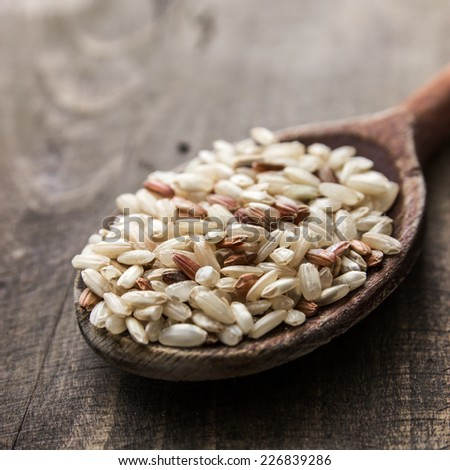 brown rice in wooden spoon on table, close up - stock photo