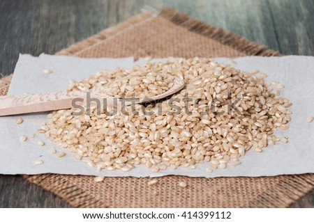 Brown rice on a tablecloth fabric sack and a wooden spoon