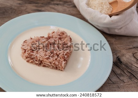 brown rice on wood background - stock photo