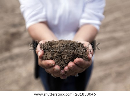 Brown rich soil in hands from agricultural area - stock photo