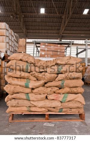 Brown sacks stack on wooden pallet in stockpile - stock photo