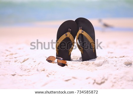 Brown sandals and shades in beach sand.