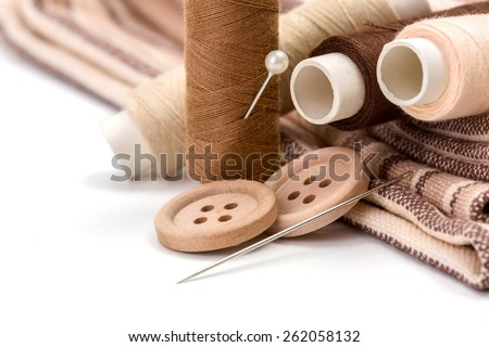 Brown sewing kit: buttons, needles, threads and materials - stock photo