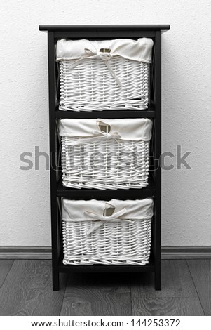 brown shelf with wicker baskets at white wall - stock photo
