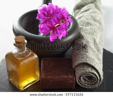 Brown soap, oil and other beauty objects over black stone - stock photo