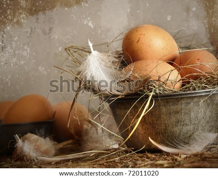 Brown speckled eggs with straw in old tin bowl - stock photo