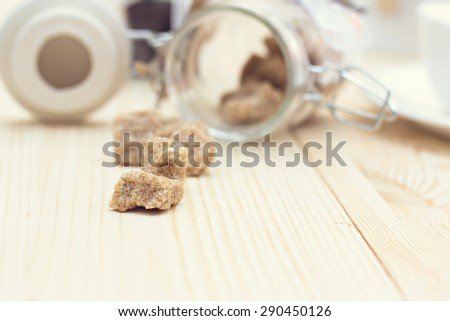Brown sugar, a few pieces.  Pieces of brown sugar spilling on the table - stock photo