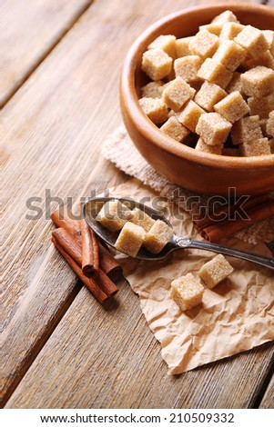 Brown sugar cubes in bowl, star anise and cinnamon sticks on wooden background