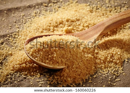 brown sugar heap and wooden spoon  - stock photo