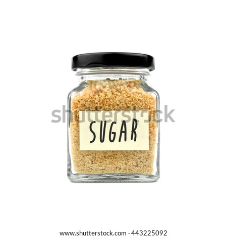 """Brown sugar in a glass bottle isolated on white background. Granulated sugar, with word """"SUGAR"""" on yellow stick note paper and black lid. Modern and stylish. Close up. - stock photo"""