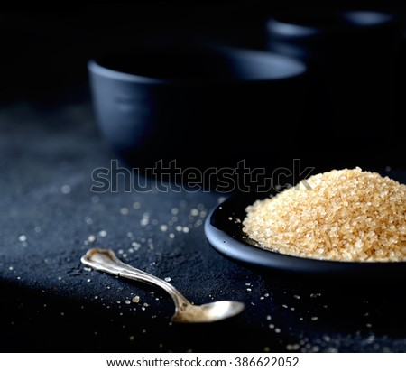 brown sugar in a saucer on the black background