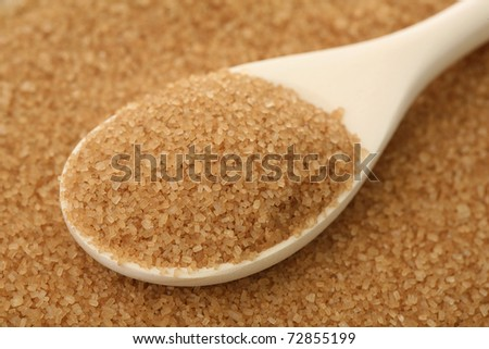 Brown sugar in a wooden spoon - stock photo