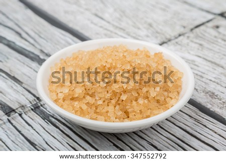 Brown sugar in white bowl over wooden background
